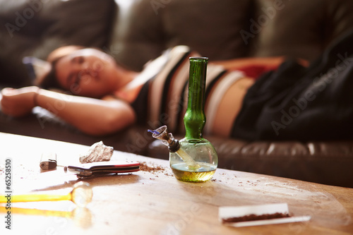 Fotografia  Woman Slumped On Sofa With Drug Paraphernalia In Foreground