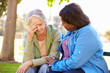 canvas print picture - Woman Comforting Unhappy Senior Friend Outdoors