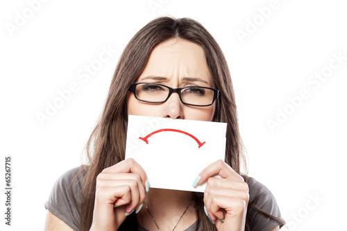 Fotografía  Muchacha triste con una triste sonrisa dibujada en un papel