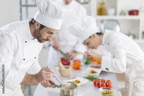 Fotografie, Obraz  Kuchař připravuje pokrm jeho tým v pozadí