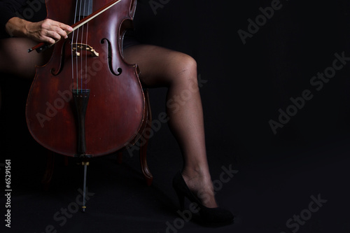 Foto Beautiful woman holding a cello with selective light and black d