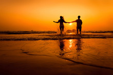 Silhouettes Of Couple Running To The Sea On The Beach At Sunset