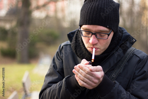 Young man relaxing in a park, smoking a cigarette #65313188