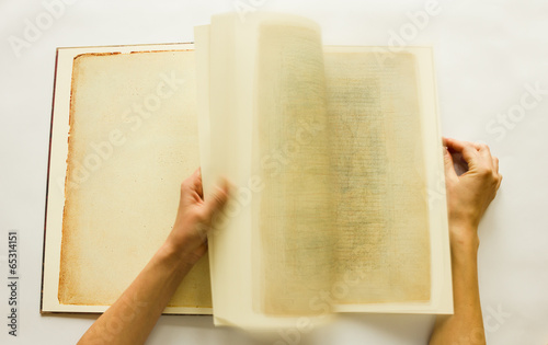 Hands turning pages of vintage book #65314151