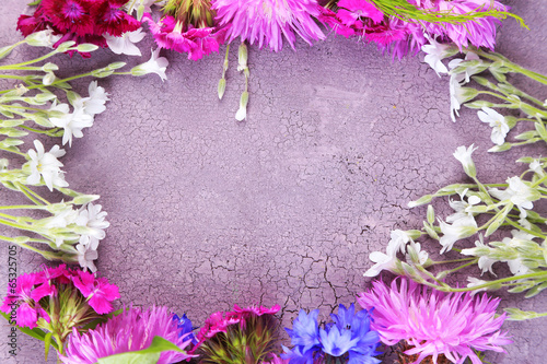Bright wildflowers on color wooden background