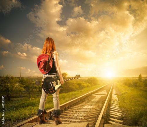 rude-kobiety-z-gitara-w-odleglosci-kolejowej-do-zachodu-slonca