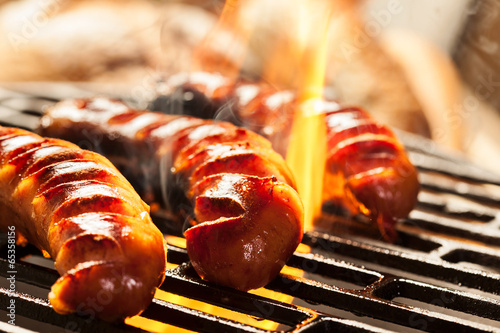 Grilling sausages on barbecue grill - 65358156