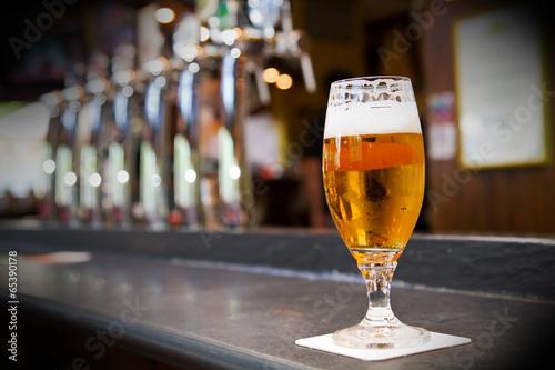Fotografie, Obraz  Glass of light beer on a dark pub
