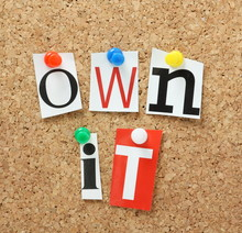 The Phrase Own It In Magazine Letters On A Cork Notice Board