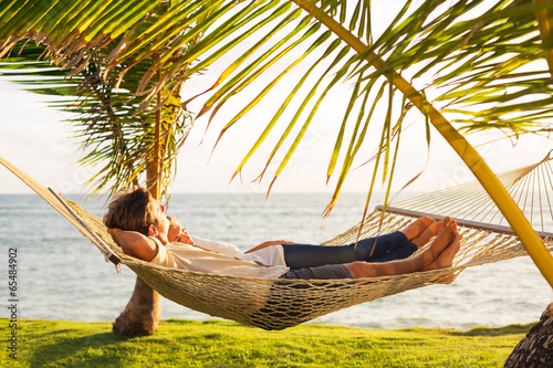 Couple relaxing in tropical hammock Poster