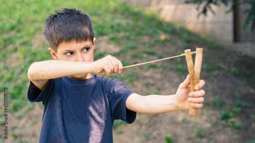Valokuva Child aiming with sling outdoors portrait.