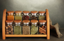 Jars With Spices On Shelf, On Table On Grey Background