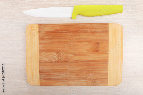 Kitchen knife and cutting board on wooden table