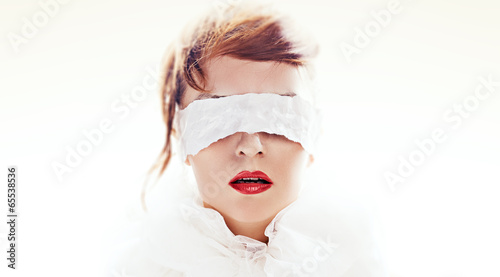 Fotografie, Obraz  Portrait of attractive woman blindfolded with white paper ribbon