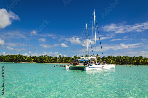 Fotografiet White catamaran on azure water against blue sky