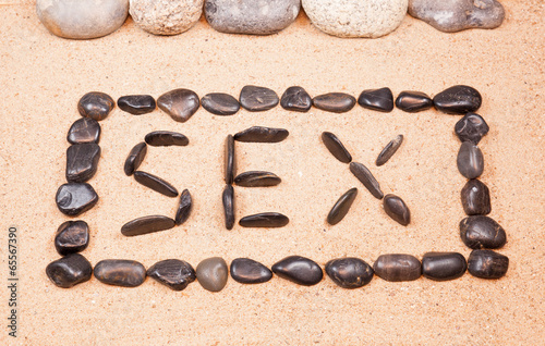 word sex written with pebbles on the sand of a beach
