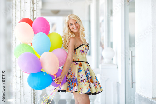 Beautiful smiling blond girl with colorful balloons Poster
