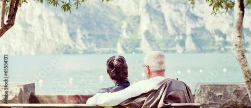 Älteres Paar sitzt gemütlich am See Canvas Print