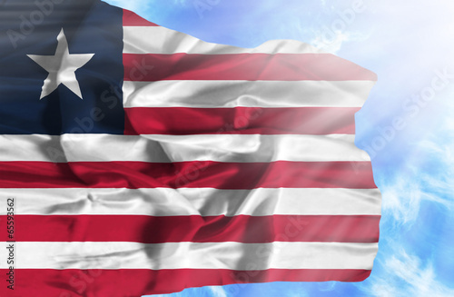 Photo Stands United States Liberia waving flag against blue sky with sunrays