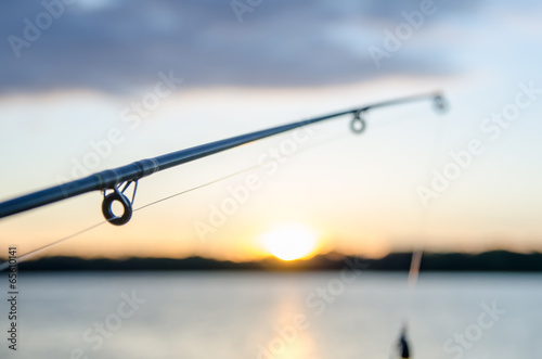 Poster Vissen fishing on a lake before sunset