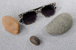Sunglasses and pebbles on the sand