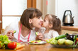 funnt mother and kid eating vegetables in kitchen