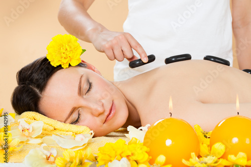 Woman Receiving Hot Stone Therapy In Spa