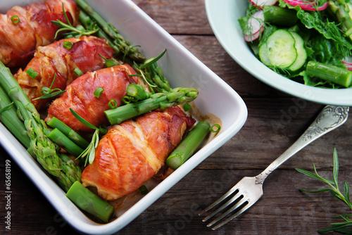 Fototapeta chicken fillet wrapped in prosciutto ham with asparagus obraz