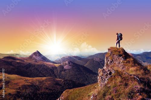 Fototapeta hiker on top of a rock looking far away obraz
