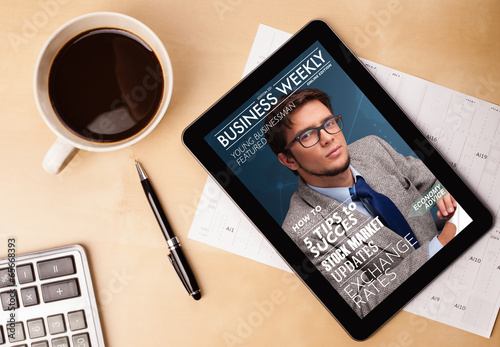 Fotografie, Obraz  Tablet pc showing magazine on screen with a cup of coffee on a d