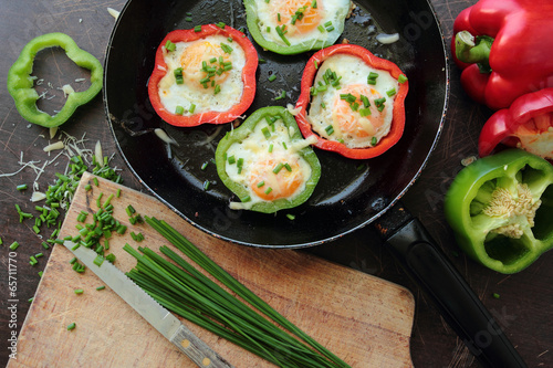 Foto op Aluminium Voorgerecht Fried eggs in colorful peppers and green chive for breakfast