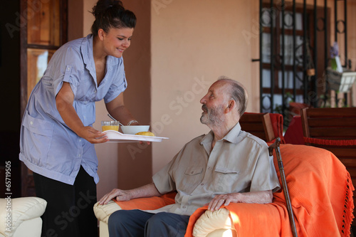 Fotografia  nurse or helper in residential home giving food to senior man
