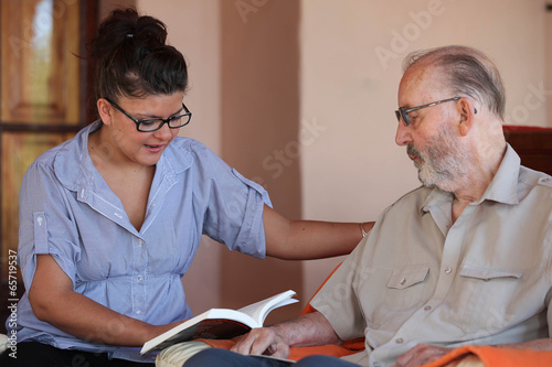 Papel de parede companion or granchild reading to senior or grandfather