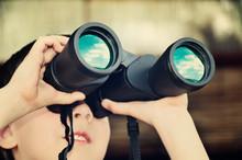 Boy Looking Through Binoculars. Toning Effect With Vanilla