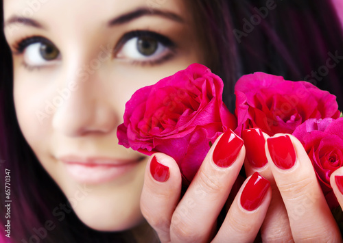 Red manicure on a woman hands with red roses. Poster