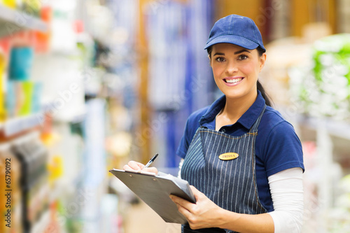 female clerk working in supermarket Fotobehang