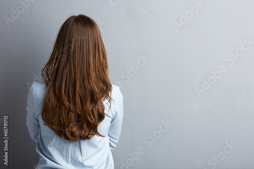 Fotografie, Obraz  Business woman standing back against gray wall.