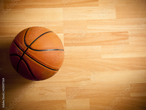 An official orange ball on a hardwood basketball court
