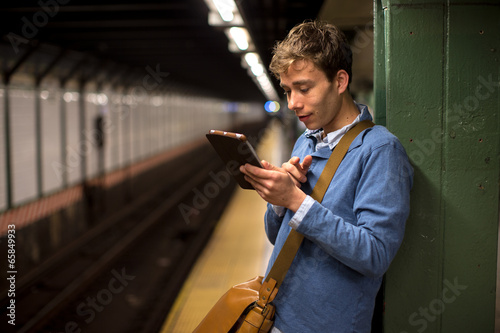 Fotografie, Obraz  Young caucasian man using tablet pc in subway station