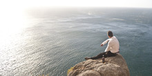 Young Handsome Guy Sitting On Rock Above Ocean