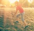 Boy climbing slope against summer sun