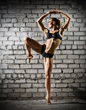 Muscular dancing woman on brick wall (dark version)