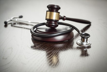 Gavel And Stethoscope On Refle...