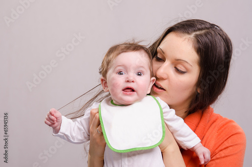 Valokuva  Six-month baby girl in bib tear your hair mom
