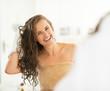 Leinwandbild Motiv Portrait of smiling young woman wiping hair with towel