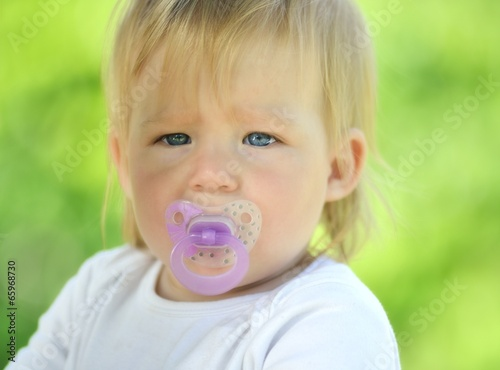 Fotografia, Obraz  Cute baby with soother in his mouth, outdoors.