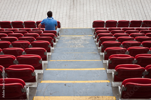 Papiers peints Stade de football Empty stadium seats with a man alone