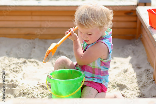 Fotografie, Obraz  Little toddler girl playing with toys in sandbox