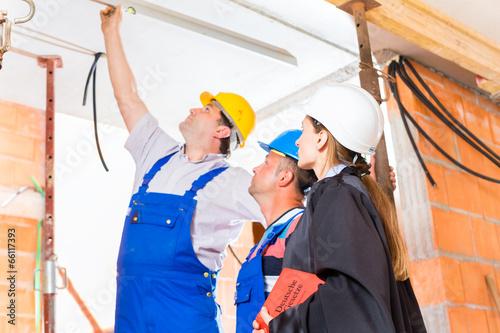 Fotografie, Obraz  Anwältin kontrolliert Baustelle auf Mängel