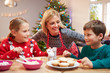 Mother And Children Decorating Christmas Cookies Together